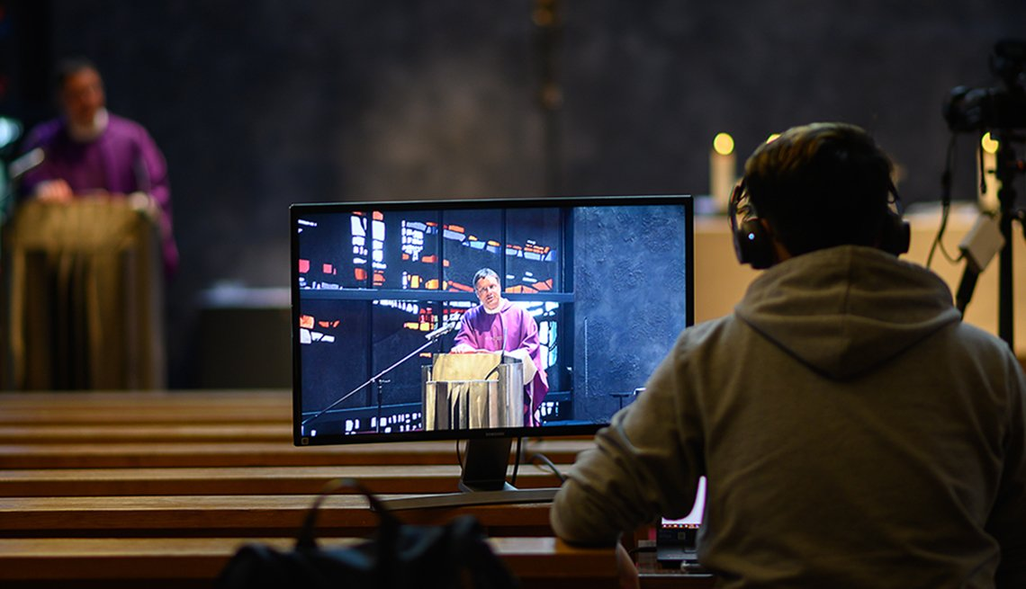 A man sitting in a church behind a computer screen wearing headphones as he records the service to live stream