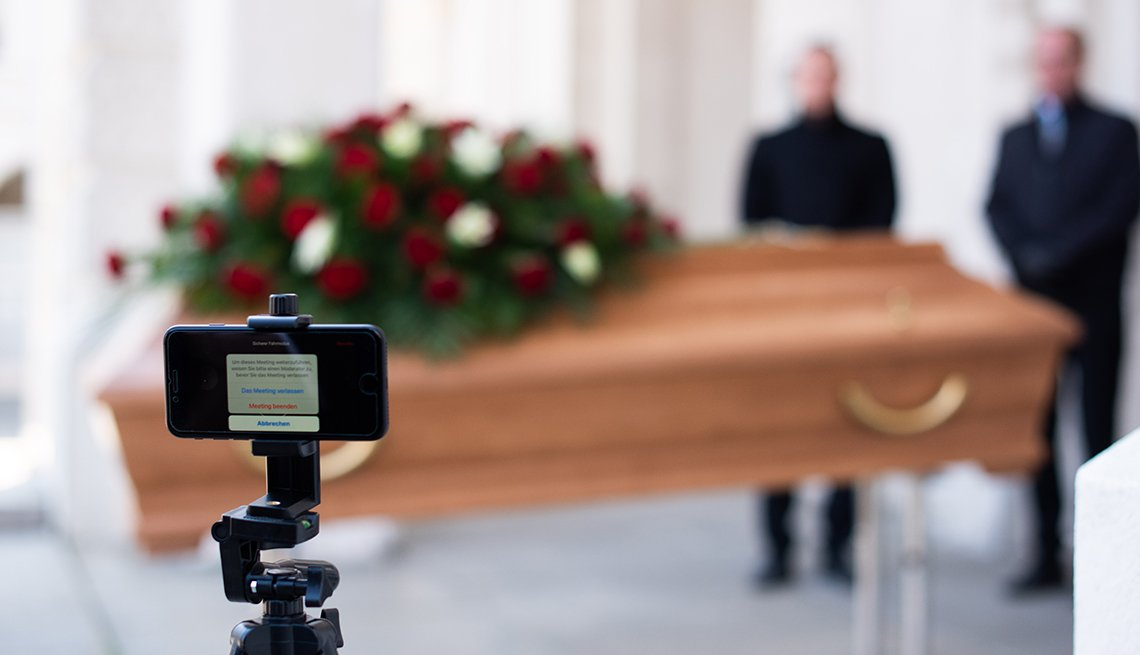 Two men standing near a casket. A video camera is in the foreground ready to  live stream the services