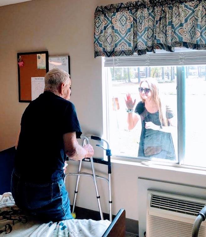 Un hombre mayor recibe una visita de su hija a través de la ventana de su unidad de la planta baja