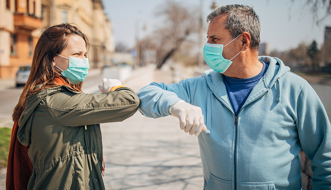 Man and woman, two people with protective masks  greeting each other with elbows instead of handshake, alternative non-contact greeting during coronavirus epidemic, standing on the street in safe distance