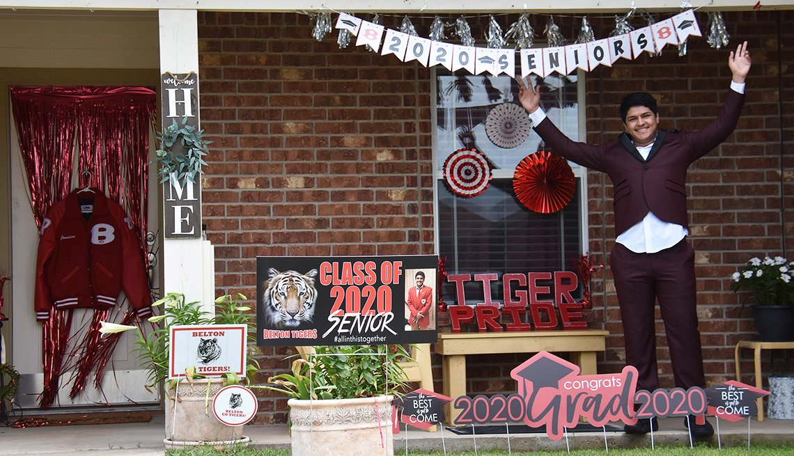Jonathan Nieves smiles on his porch, decorated with 2020 Grad memorabilia