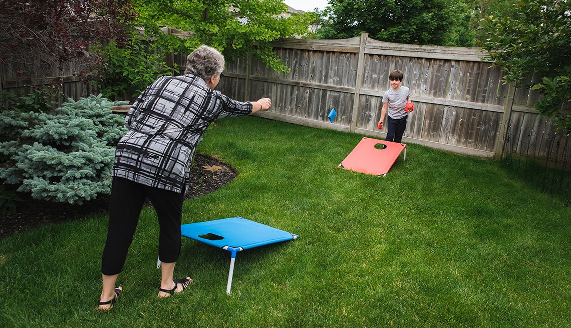 woman playing cornhole with grandson in a fenced yard