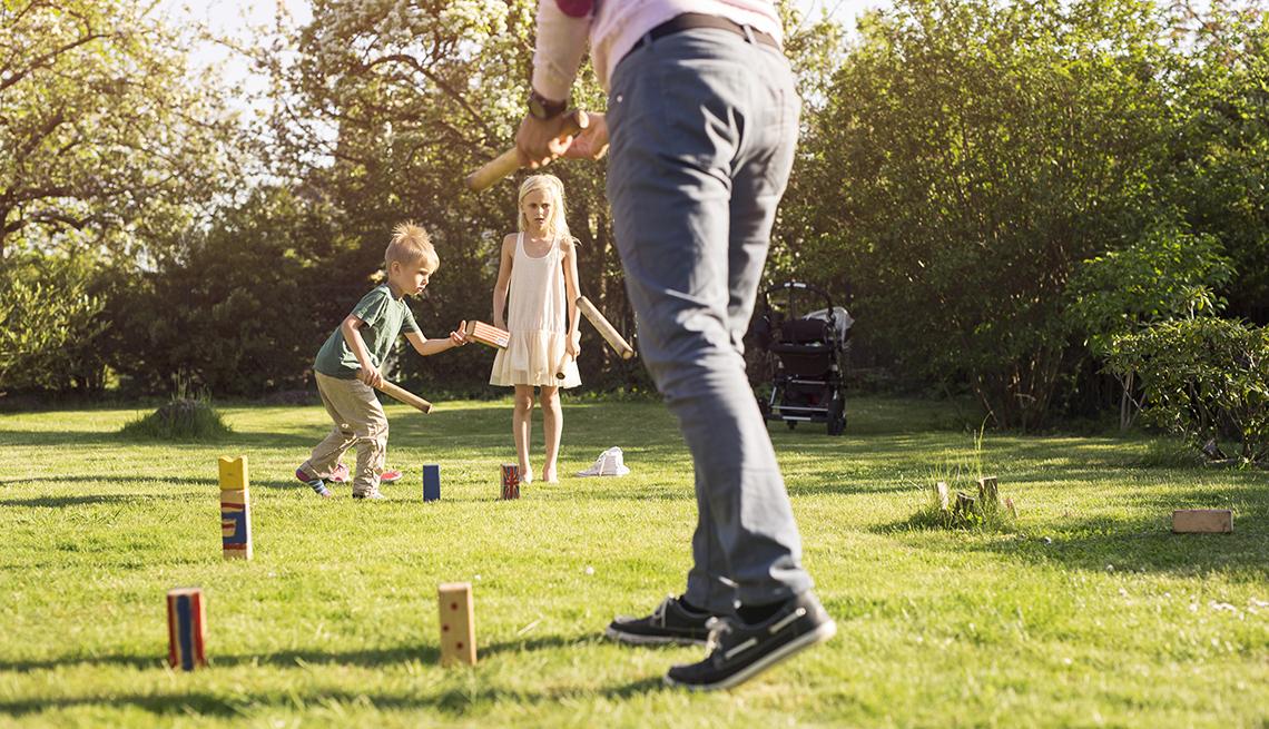 item 8 of Gallery image - Dos niños pequeños y un hombre en un patio juegan el juego de césped kubb