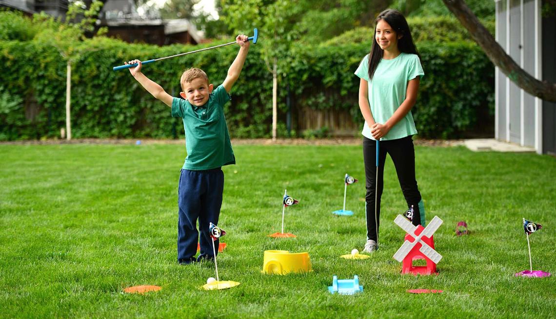 item 10 of Gallery image - Un niño y una niña juegan minigolf en el patio trasero de su casa