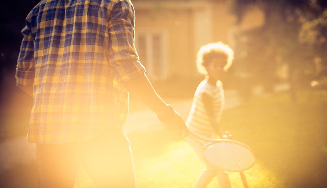 Un hombre y una niña jugando con raquetas