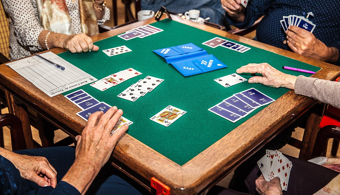 Adults gathered around a table playing the bridge card game