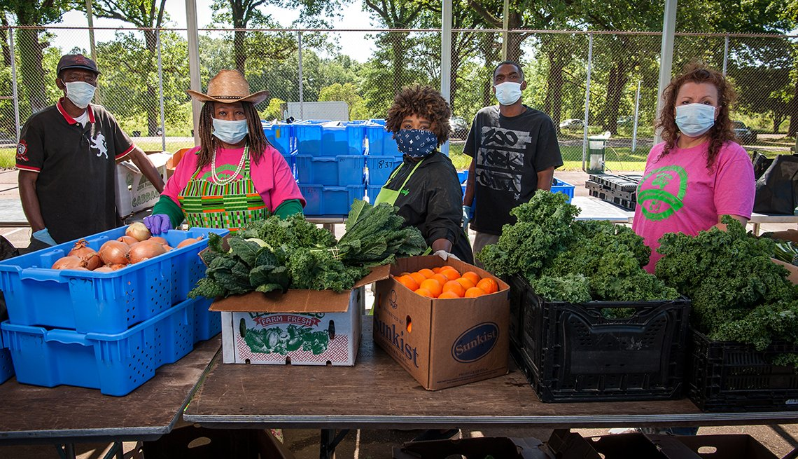 doctor cindy ayers elliott and her farm staff stand behind a table full of produce wearing covid face masks