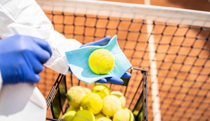 Una persona desinfecta pelotas de tenis