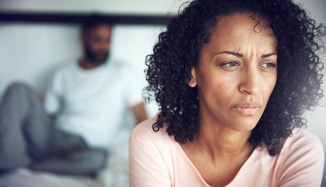 Imagen de una mujer en la habitación de su casa que parece molesta con su marido