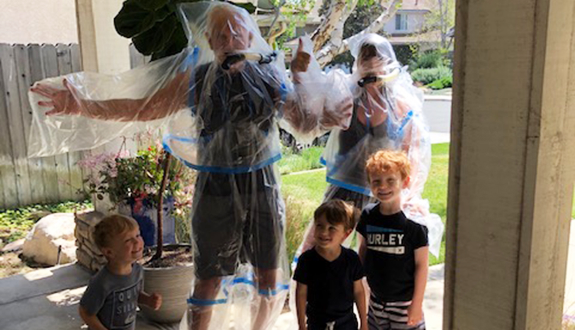 Abuelos en traje de plástico posan para una foto con sus nietos