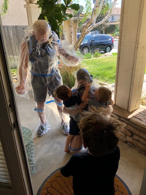 Daria and her husband greet her grandchildren wearing a bubble suit