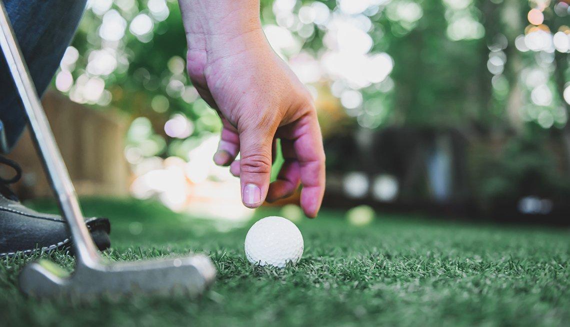 Imagen de una mano alcanzando una pelota de golf en el suelo con un palo de golf