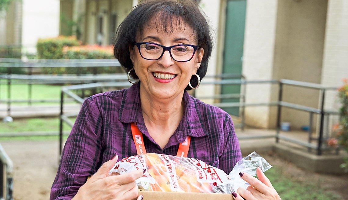 Mary Lustri sostiene una caja de comestibles