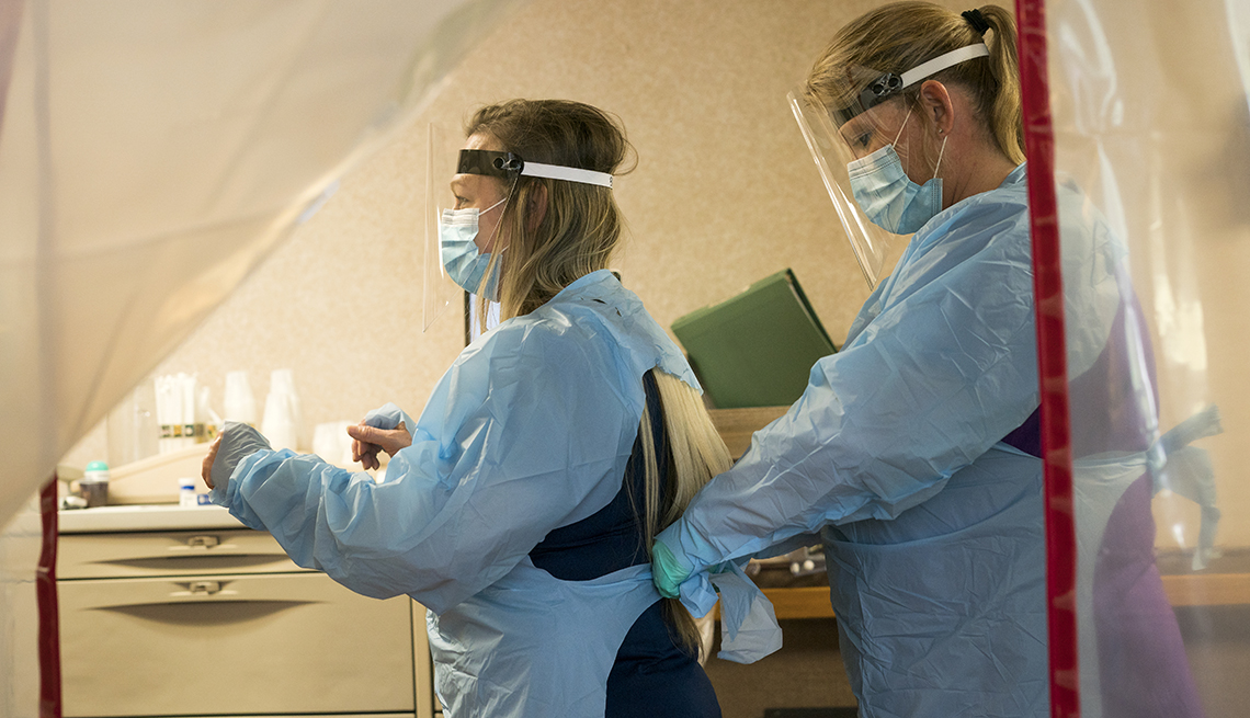 Two nurses don PPE protective gear of plastic gowns, face masks, face shields and gloves prior to entering a quarantined patient's room in isolation during the Covid-19 pandemic, Midwest, USA