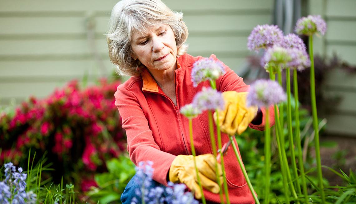 Mujer en el jardín cortando flores