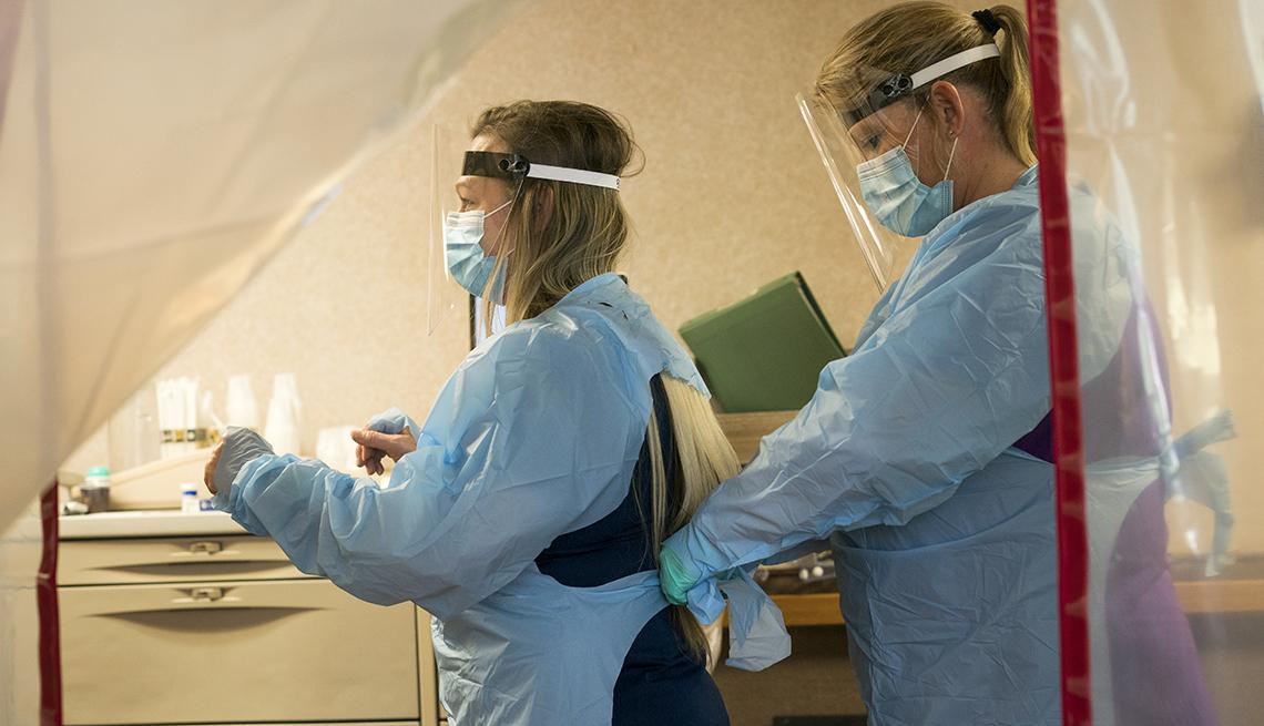 Dos enfermeras se ponen el equipo de protección antes de entrar a una habitación