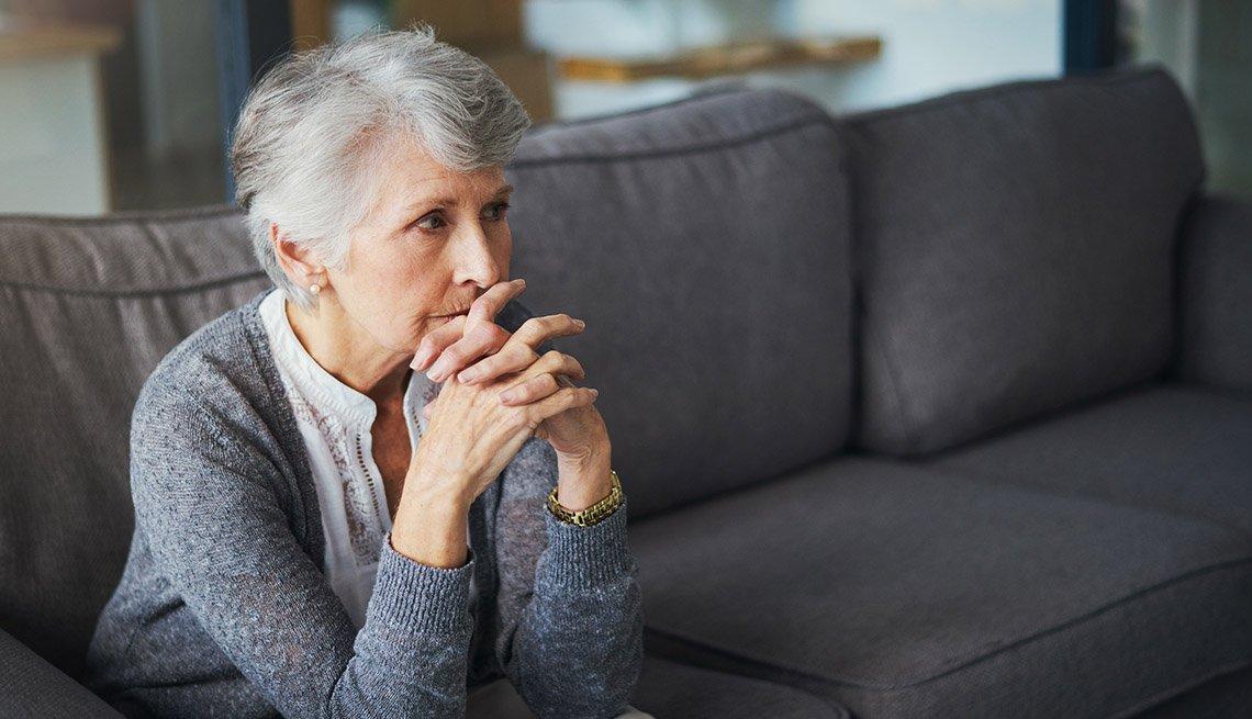 Mujer mayor sentada en el sofá con las manos juntas
