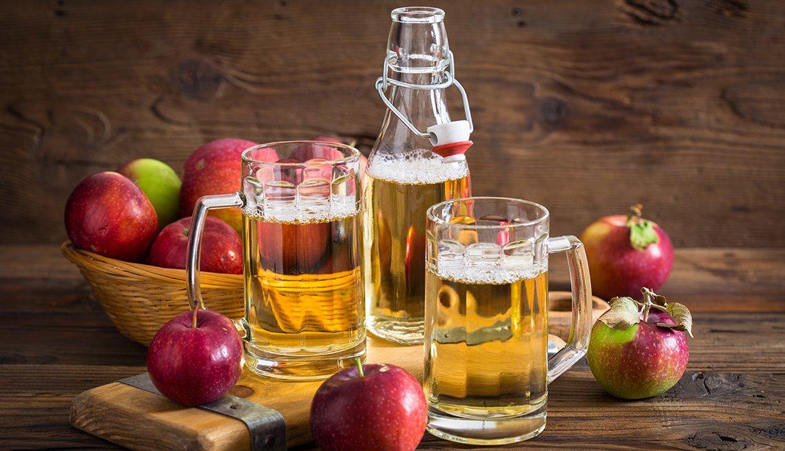 Sidra de manzana en jarras de cerveza rodeadas de manzanas sobre un fondo de madera