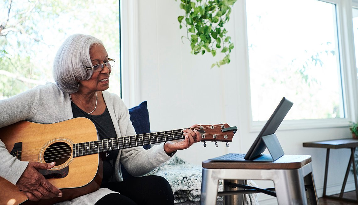 Woman learning to play a guitar on her tablet device