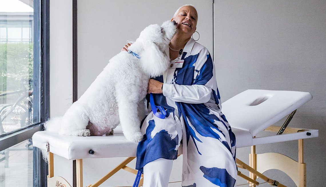 woman sitting on massage table hugging a big poodle dog