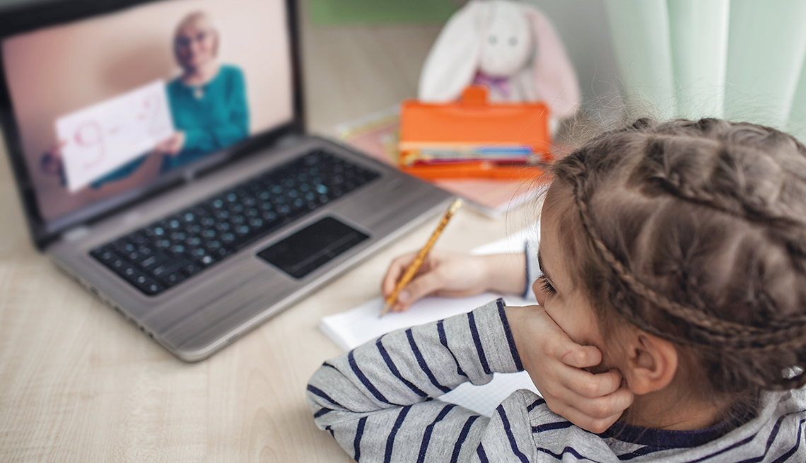 Schoolgirl studying homework math during her online lesson at home, social distance during quarantine, self-isolation, online education concept, home schooler