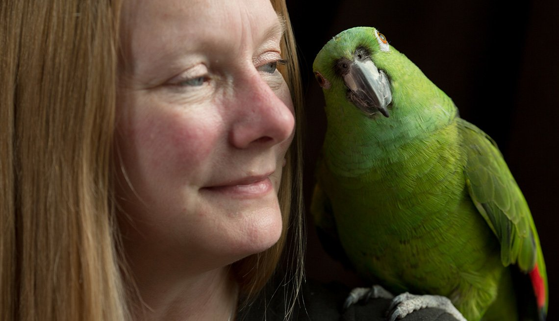 item 2 of Gallery image - close up of woman with green parakeet on her shoulder