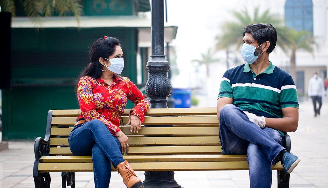 Una mujer y un hombre con máscaras sentados en una silla del parque