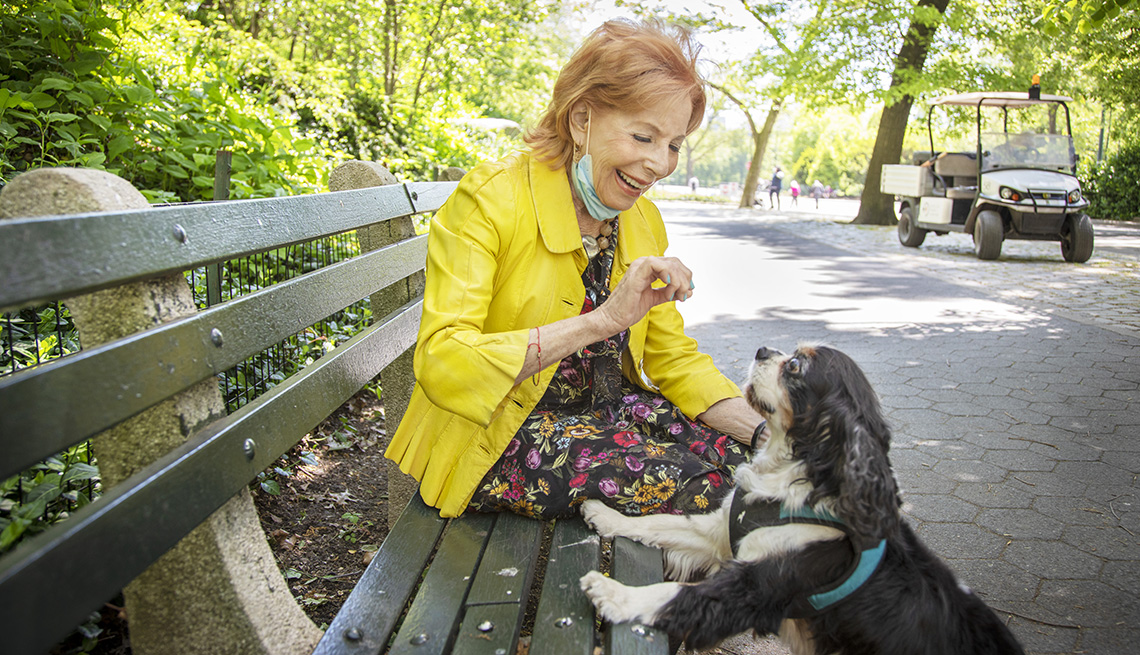 woman sitting on park bench holding a treat for her dog who has its front paws up on the bench looking at her