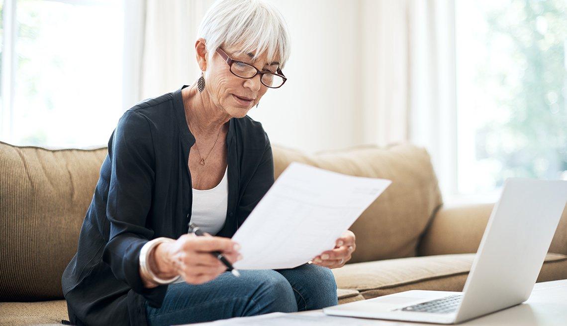 Una mujer sentada en el sofá frente a su computadora mirando un documento impreso