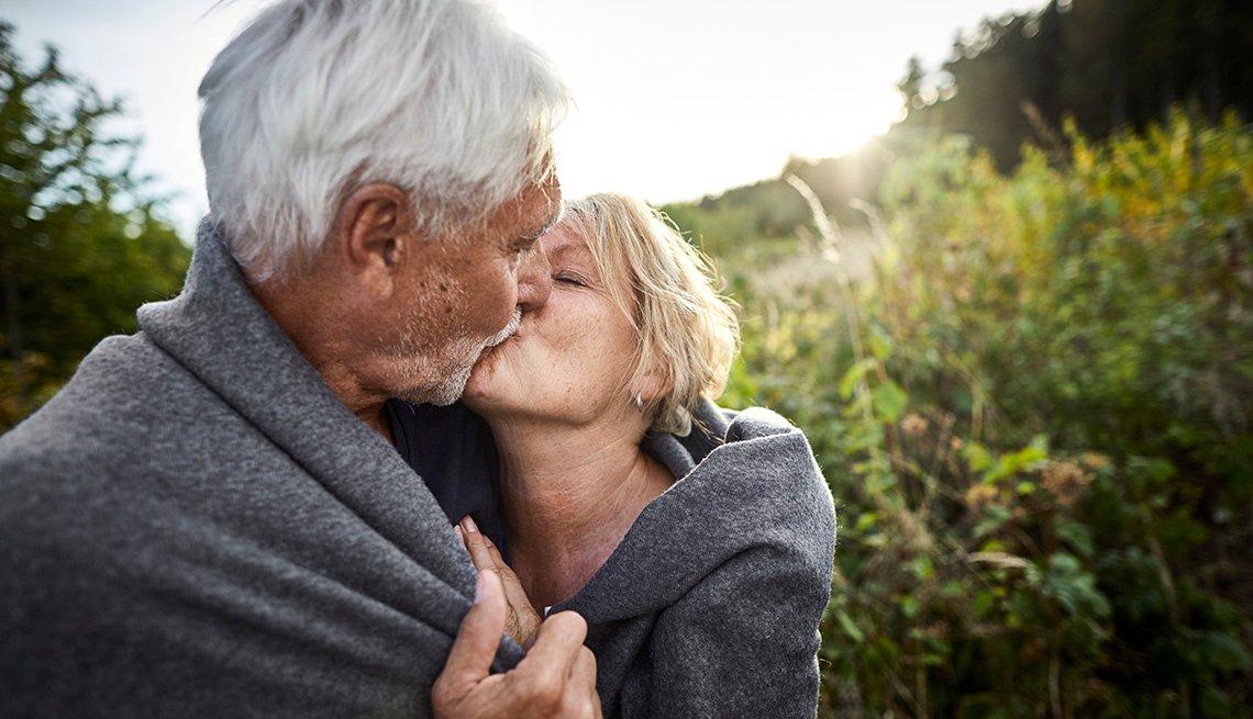 Una pareja de adultos mayores se arropan con una manta y se dan un beso