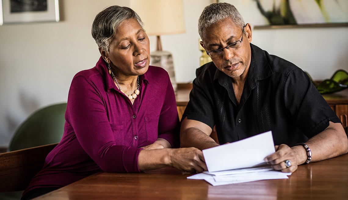 Couple looking reviewing 401k documents at home