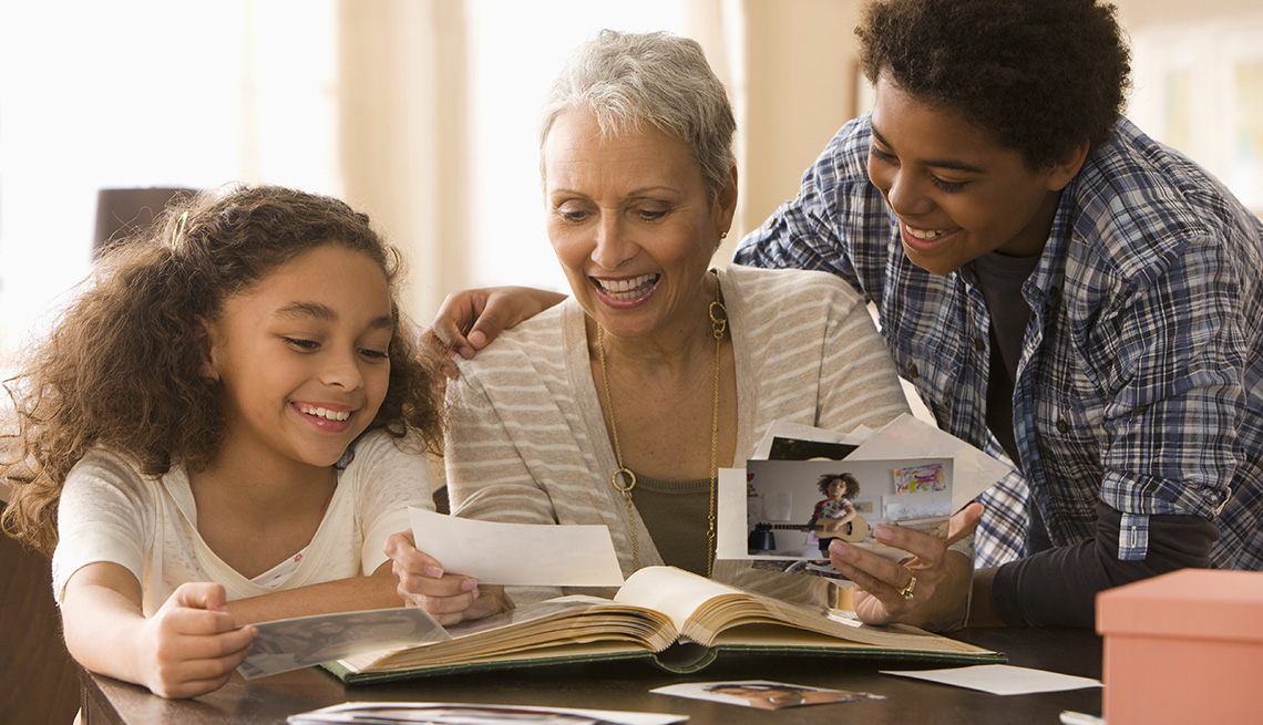 Grandmother and grandchildren looking at photographs