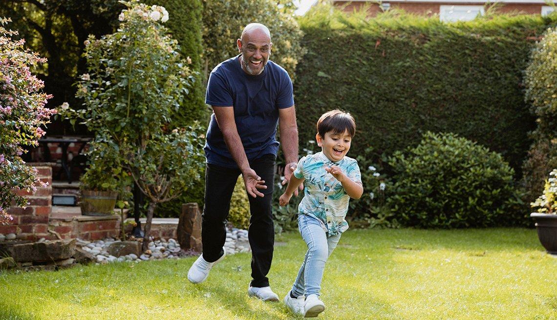 Abuelo persiguiendo a su nieto en el jardín mientras juegan al aire libre