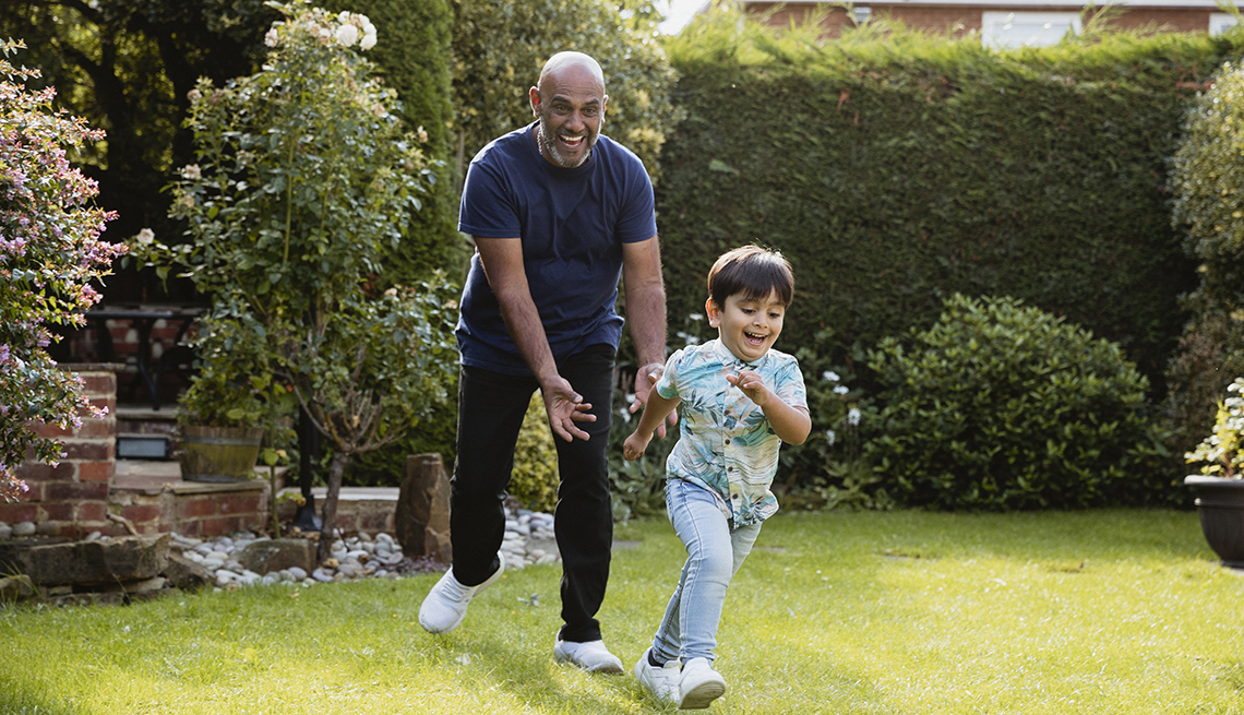Grandad chasing grandson in the garden during outdoors playtime.