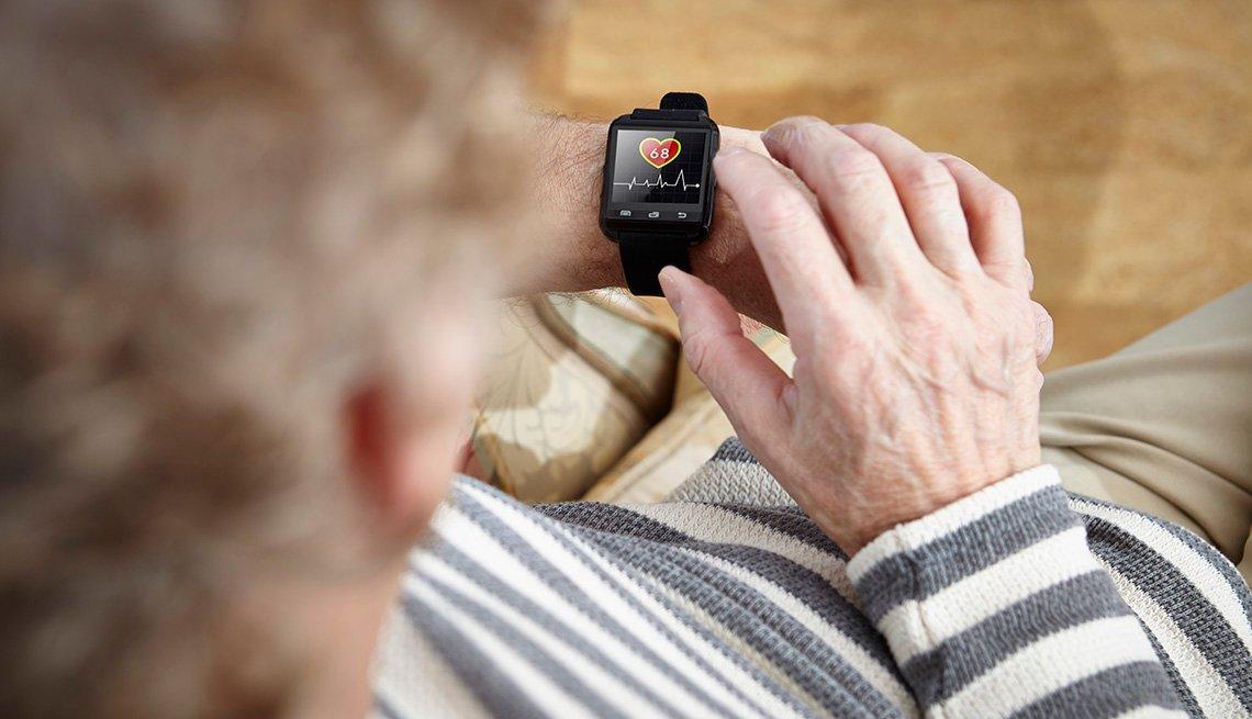 Un hombre mayor sentado en un sillón observa su reloj inteligente o smartwatch