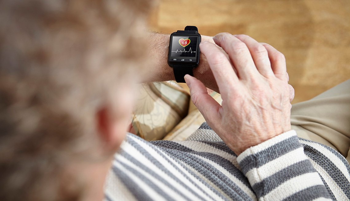 Older adult sitting in armchair using smartwatch