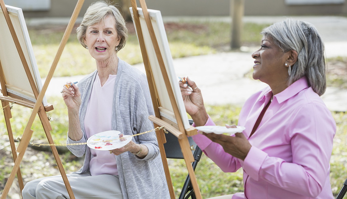 Two women taking an art class outdoors. They are sitting at easels, painting on a canvas.