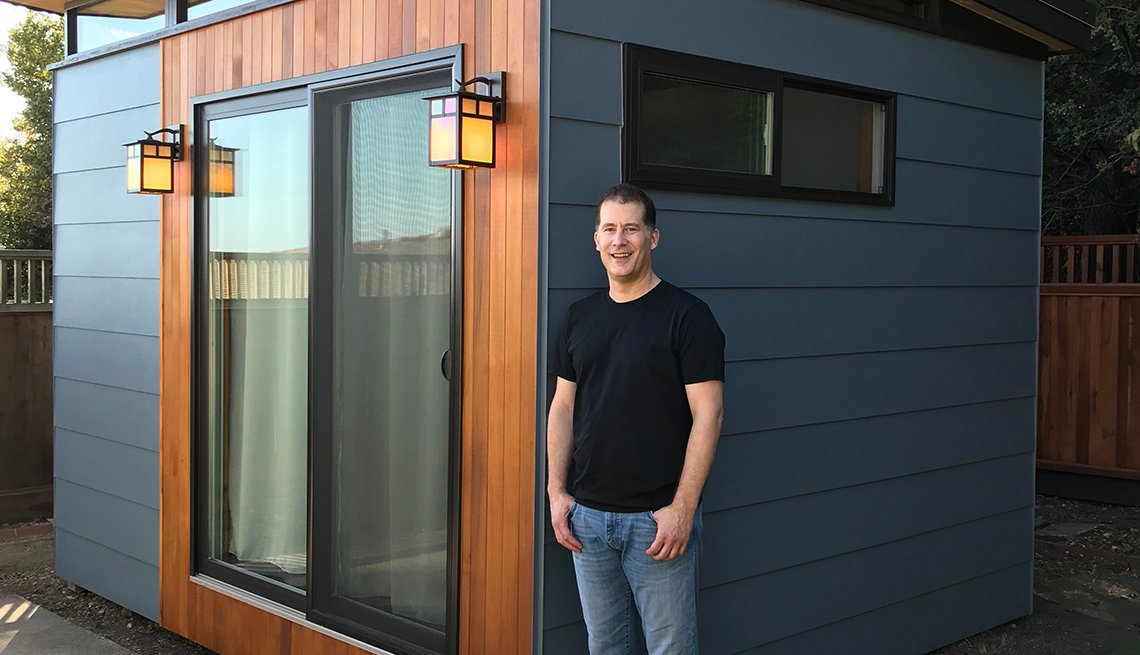 Un hombre parado junto a una unidad de vivienda complementaria