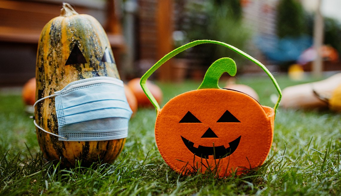 Pumpkins on the grass with face protective mask during Covid-19 pandemic