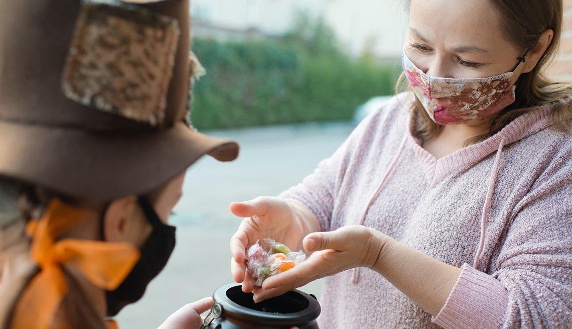 Niña que usa máscara recibe caramelos durante Halloween