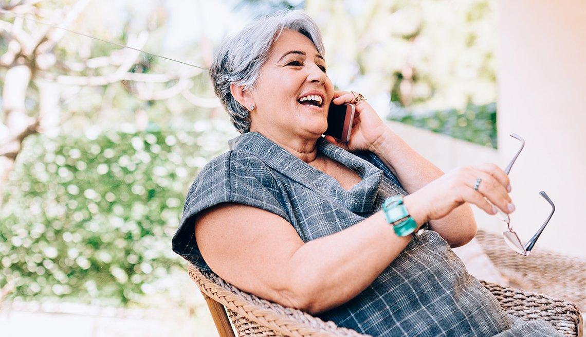 Una mujer sonríe mientras habla por teléfono