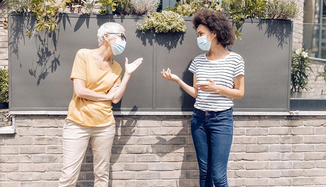 Dos mujeres que usan mascarillas sostienen una conversación