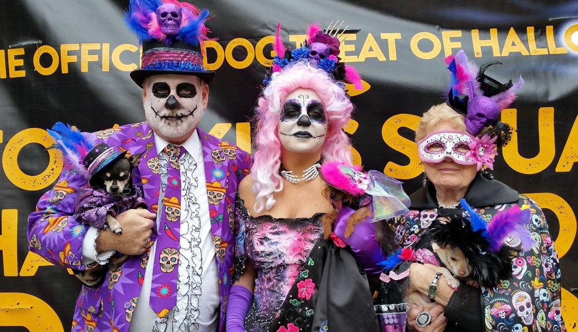 Un grupo de personas con sus mascotas disfrazadas para Halloween con disfraces relacionados al Día de los Muertos