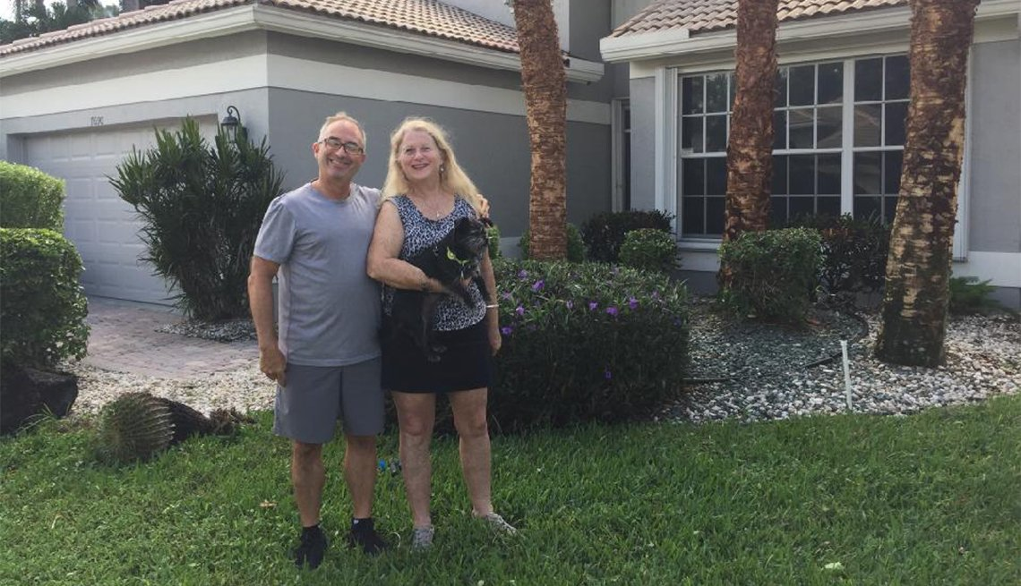 David and Ellen Comisar(holding their dog Kiwi) in front of their new Delray Beach home.