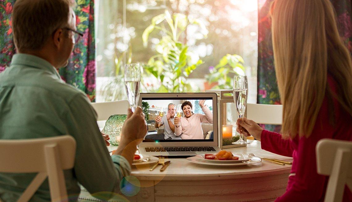 Hombre y mujer sentados en la mesa del comedor, cenando, bebiendo champán y teniendo una videollamada