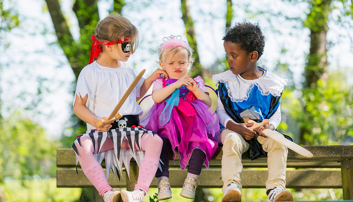 Three children sitting on a park bench wearing homemade halloween costume