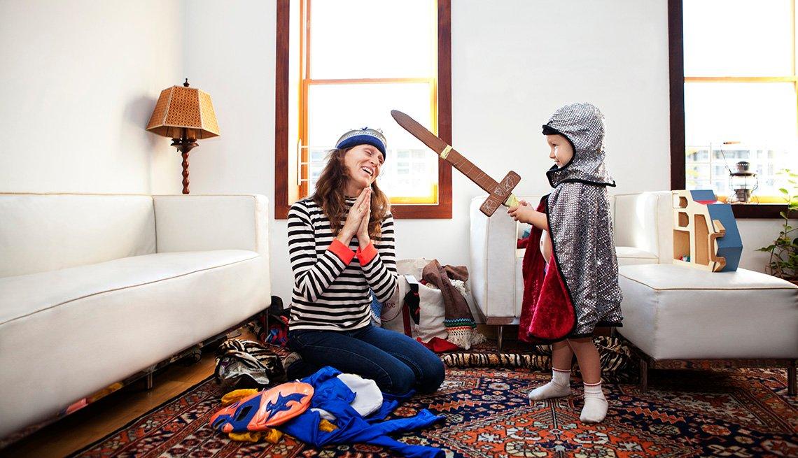 Madre e hijo jugando en la sala de su casa. El niño está vestido con un disfraz de caballero.