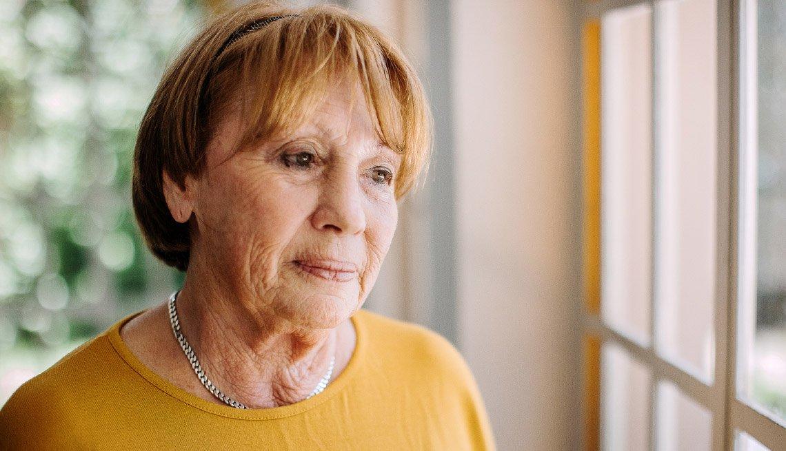 Mujer mayor mira con tristeza por la ventana
