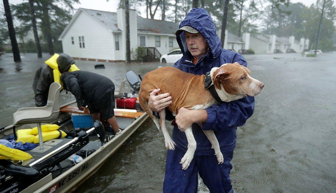 Un hombre sostiene una mascota en una calle inundada con un pequeño bote cerca