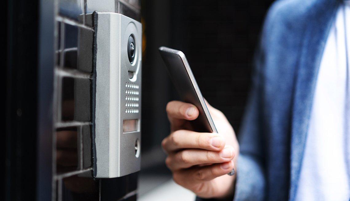 Una persona sostiene su teléfono frente a una cerradura inteligente